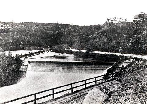 MELLOMDAMMEN. Mellomdammen under en flom på 1870-tallet med nedkjøringen fra Bøkelia i forgrunnen.