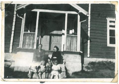 Familien Romsdal fra Alta på trappa til snekkerskolen på Krokhaug sommeren 1945. Familien bodde i et rom på snekkerskoleloftet.