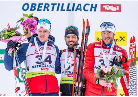 Sivert Bakken på pallen i Obertillach sammen med vinneren av normalprogrammet, Simon Fourcade og tredjemann Sergey Bocharnikov.