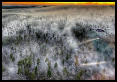 SKOGBRANN: Her dumper et helikopter vann over en skogbrann i Sverige. Svenske myndigheter har bedt om bistand fra utlandet for å få bukt med flammene.