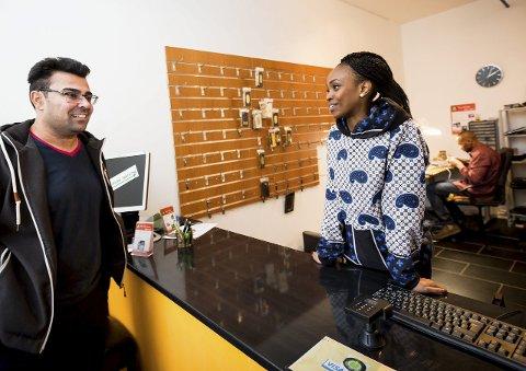 Ismail Palani har en ødelagt mobil. Stella Mwangi hjelper ham gjerne. Hun har ikke lagt musikken på hylla, bare funnet ut at hun kan gjøre mye mer. – Jeg har alltid hatt interesse for å drive forretning, forteller den ferske markedsdirektøren. FOTO: Lisbeth Andresen