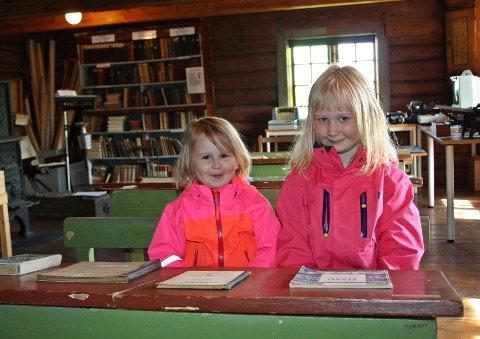 NYSGJERRIGE: Lilli Marie Dahl (3) og Emma Johanne Dahl (7) tester skolestuas skrivepulter fra rundt 1800- til tidlig 1900-tallet.