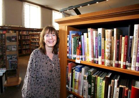 TRAVELT PÅ SOMMEREN: Avdelingsleder Hanne Utne forklarer at det er ekstra mange som tar turen på biblioteket i fellesferien.