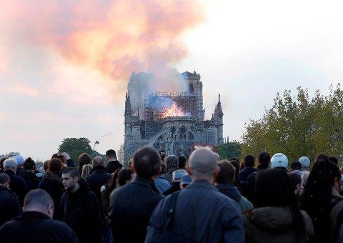 Turister og parisere ser at flammer stiger opp fra Notre-Dame-katedralen i Paris. Store mengder gulbrun røyk fyller luften over katedralen.
