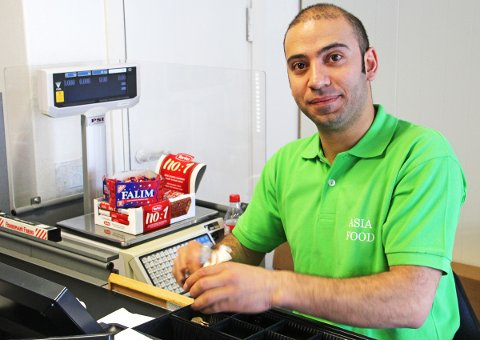 Ali Teker, innehaver av Asia Food, ved kassen i nyåpnet matvarebutikk i Sandnessjøen.