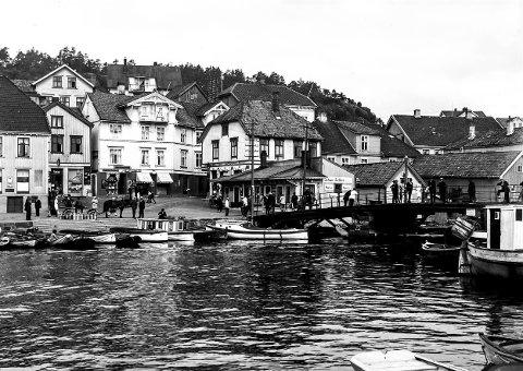 Bybrua og Jens Lauersøns plass: Dette bildet må være tatt enten sent på 1920- eller på 1930-tallet. Bildet har fanget den spesielle stemningen som var i Kragerø på den tiden og forteller en god del. En hest står ved trappene ned til Asbjørnsens brygge. Trolig skal den hente de store melkespannene som står oppstilt og frakte melken til meieriet på Andølingen. På Bybrua står folk og prater og kikker på båtlivet. Helt til venstre kan man se hjørnet av Kringsjågården, som ble tatt ned og flyttet til Valberg midt på 1960-tallet.