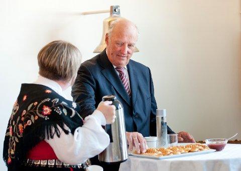 Kong Harald forsyner seg med vafler under feiringen av Sjømannskirkens 150-årsjubileum i Bergen i 2014. Møyfrid Seglem står for kaffeserveringen.