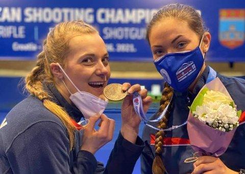 BLIDE JENTER: Katrine Aannestad Lund (t.v.) sjekker bronsemedaljen til Jeanette Hegg Duestad etter EM-finalen i matchskyting. FOTO: NORGES SKYTTERFORBUND