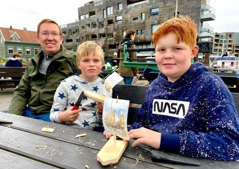 BÅTBYGGERE: Peter Kristian (12) og Ole Reidar (7), sammen med pappa Bjarne Øwre hadde god kontroll på båtbygginga på kaia ved Polarmuseet.