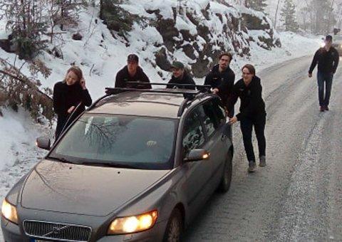 Flere av spillerne fra Ringerike Panthers skyver en bil på glattisen på Åsaveien slik at de kan komme seg videre til kamp.