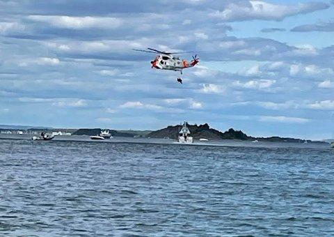 REDDET: Her blir en person heist opp i redningshelikopteret. Totalt ble to personer reddet opp.
