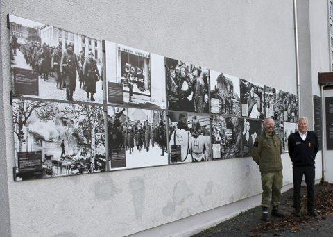 Omviser Bjørn Terjesen (t.h.) og sjef ved Bergenhus Festningsmuseum, major Harald Gåsø viser frem plakatutstillingen på museumsveggen. Foto: TOM R. HJERTHOLM