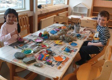 GLEDE: De eldste barna i Liland barnehage har båret flere kilo stein opp fra fjæra. Steinene er malt i alle regnbuens farger. De voksne har skrevet oppmuntrende ord på steinene, og nå blir de plassert rundt i Evenes for å skape glede. På bildet er fem år gamle Khadijah Mahboubi og Sander Jensen.