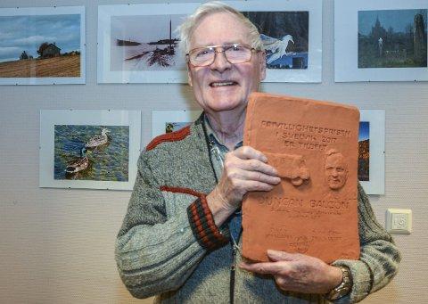 DEN FØRSTE: Duncan Balcon ble den første mottakeren av Frivillighetsprisen. Diplomet er et relieff laget av Marit Wiklund. I bakgrunnen ser man noen av fotografier han selv har tatt. Foruten en bokutgivelse, henger de også i Frivilligsentralen.