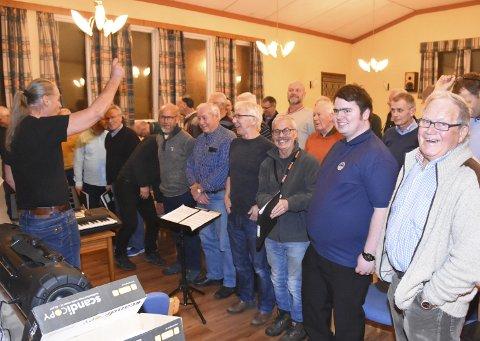ØVER TIL KONSERT: Her i bedehuset på Nordlandet har de øvd til den store korkonserten den 10. desember. Dirigent Erik Glærum (foran) har full kontroll på korgjengen.