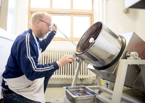 Håndarbeid: Det er ikke mye avansert maskineri i den nye sjokoladefabrikken på i Damsgårdsveien, det meste foregår for hånd. Her heller Carlo Eugen Johannessen sjokolademassen fra «concheren» og over i store former. Nå skal sjokoladen lagres en måned før den tempereres og formes til plater. FOTO:Skjalg Ekeland