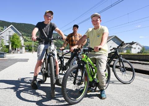 NY BEDRIFT: 14-åringene Erik Kleiven (t.v.) og Torje Husom Torgersen skal stå for inn- og utlevering av syklene i Ringebu i sommer. Hans Anton Torgersen (bak) ved Værfast er én av fire eiere i det nye firmaet Dølabike som skal leie ut elsyklene.