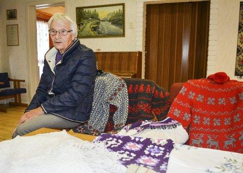FLITTIG: Mary Østreng (87) gleder seg til nok en basar i Aurskog Sanitetsforening. Det er et av årets høydepunkt. Hun har bidratt med duker til basaren i mange år. Hvor mange har hun ikke tall på. Her med et lite utvalg tepper, duker og hjemmestrikkede gensere fra både henne selv og andre medlemmer. Foto: Anne Enger Mjåland