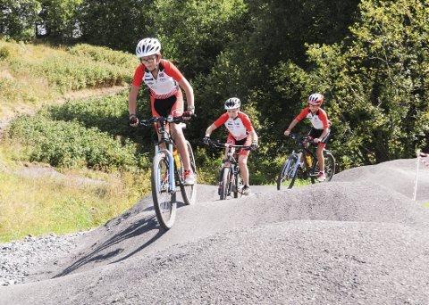 Utfordring: Sondre Nordbø (foran), Audun Dahl Jensen og Håkon Nordbø fra Sørumsand har i ferien hjulpet Bingsfoss sykkelklubb med å ferdigstille sykkelbanen. I pausene har det vært gode muligheter for å prøve ut anlegget til rundt 800.000 kroner.