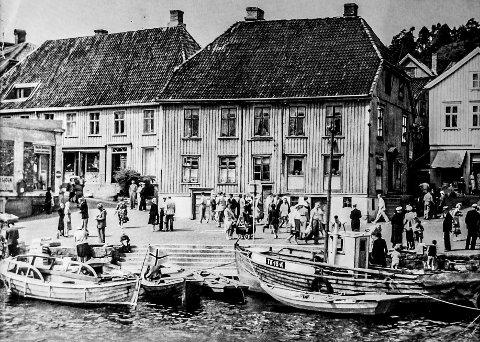 Jens Lauersøns plass først i 1950 åra: Dette bildet må være tatt kort tid etter krigen. En sommerdag i Kragerø på 50-tallet. Mye folk i byen og det ligger en del båter langs bryggene. På bildet sees en fiskebåt som sikkert flere husker. Fiskeren bodde visstnok på Øya. Midt i bildet ligger den gamle Kringsjågården, eller Rendtlergården som den også ble kalt. Gården ble revet i 1963.