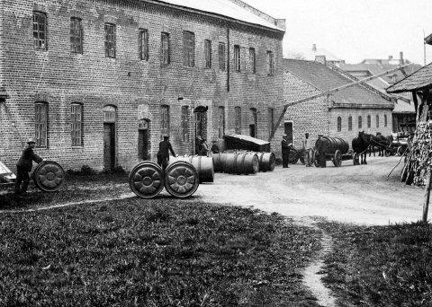 HOLMEN: Aktiviteten var stor ved Holmen Brænderi på Gjøvik. Her et bilde fra etter at man tok i bruk jerntønner til å frakte råspriten på 1800-tallet. Foto: Mjøsmuseet
