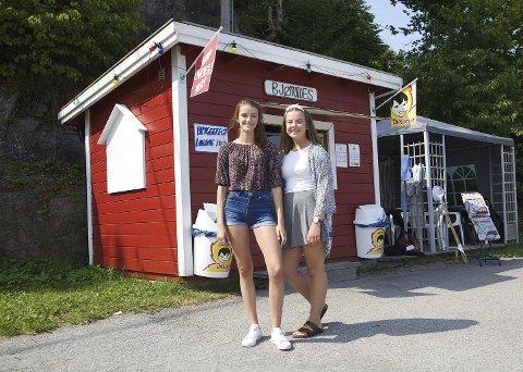 Martine Karsten (15) fra Asker og Maja Bolstad Aasgrav (15) fra Bjønnes står bak disken på Bjønnes-kiosken i sommer.