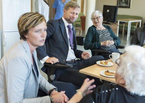 Maren Blom (med ryggen til snakker med helseminister Bent Høie (H), kommunalsjef Christine Myhre Bråthen og beboer Laila Nilsen om hvordan det er å bo på Fossetorget. Blom ønsker seg flere ansatte som har tid til å prate.