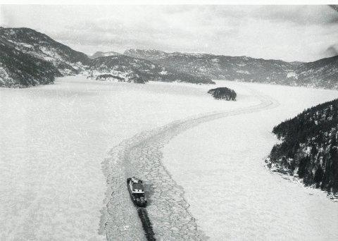 OVER TINNSJØEN: Ferge på veg gjennom råka over Tinnsjøen. Busnesgrend inn til venstre. Foto: Norsk Hydros arkiv, Riksarkivet.