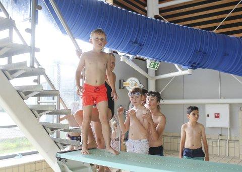 Klar for triks: Sigurd Berg Maus (7) er klar for å ta salto ut i bassenget på Østfoldbadet. Han liker godt å bade inne når været er grått – og er ikke alene om det. Tirsdag ettermiddag var det stor trafikk på badelandet.