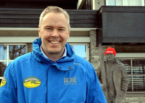 Kan smile bredt: Direktør Atle Hovi i Beitostølen Resort er veldig fornøyd med de økonomiske resultatene for 2016. Bak ser vi statuen etter pappa Steinar, som i anledning Ridderuka har fått rød topplue.