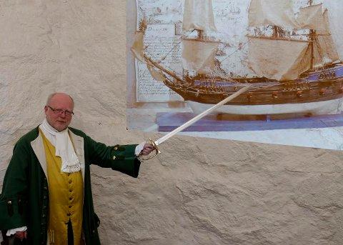 Tor Ulsnæs i 1700-tallsdrakt og med svensk kårde som pekestokk. Foto: Gaute Jacobsen/Østfoldmuseene