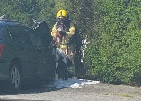 BRANN: Det skal ha vært åpne flammer fra bilen. Her har brannmannskapene fått kontroll.