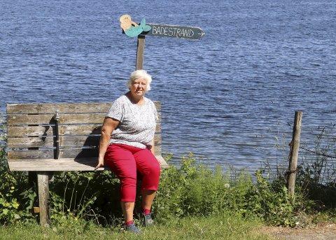 I 30 år: Anne Marie Svendsrud fra Hokksund kan ikke tenke seg et bedre sted å være. Det er faktisk hun som har laget skiltet på krakken som viser vei ned til Sandsletta, kystledhytta og stranden. Foto: Pål Nordby