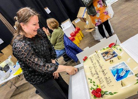 Latter og gråt: Det ble litt mye følelser for Katrine Bruun Lyngås da hun ble bedt om å skjøre den første biten av kaka. Hun var den som satte den første vaksina i Lier i januar, noe det var bilde av på kaka.