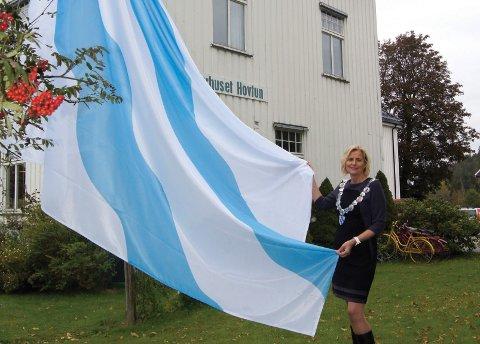 FIRER FLAGG: På forsiden av Årbok for Hurum 2019 firer ordfører Monica Vee Bratlie kommuneflagget ved det gamle kommunehuset på Klokkarstua.