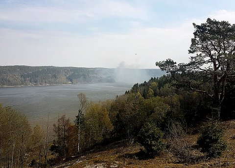 Brannrøyken velter opp på andre siden av Glomma i Glennetangen-området.