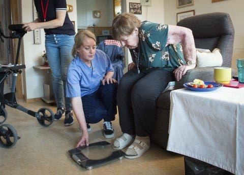 – Dere må hjelpe meg opp på vekten. Jeg klarer ikke det alene, sier Gerda Almestad. Hjemmetjenesten har rutine på å veie alle brukerne én gang i måneden. Dersom man ufrivillig går ned tre kilo i vekt, går alarmen. Her gjør sykepleier Nina Dahl klar vekten.