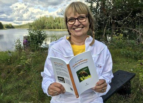 BIRØKTEREN: Forfatter Siv Henningstad med sin ferske bok om bier og honning: – Jeg elsker honning, derfor ble jeg birøkter! Biene hennes bor i kubene sine på Finnskogen.
