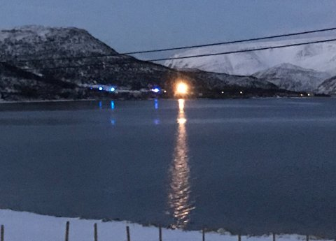 I det fjerne kunne man se blålysene og det kraftige lyset fra helikopteret tirsdag. Bildet er tatt fra området der det tidligere var eldresenter.