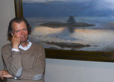 Per Trygve Lundgren ved maleriet hvor han har skildret utsikten fra hytta på Ørvik.