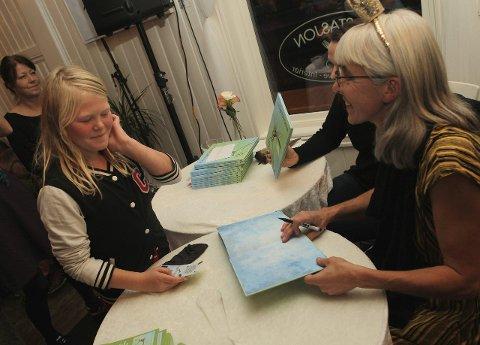 SIGNATUR: Thea (6) får Synnøve Borgens signatur i den rykende ferske «Kongeøyenstikker».FOTO: ODD INGE RAND
