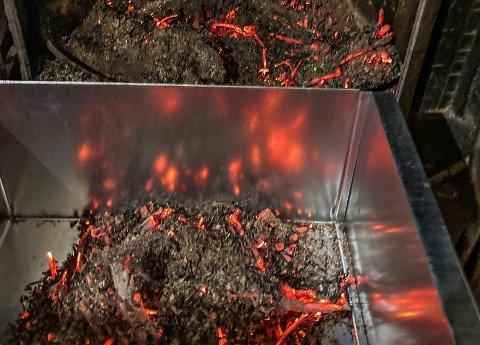 ILDMØRJE: Varmen som oppsto inne i ovnen etter at beboeren hadde stappet inn den knusktørre julegrana var ekstrem. Og gnistregnet sto opp gjennom pipa. Bildet viser restene av ildmørja i ovnen, og metallkassen brannvesenet brukte for å fjerne glørne.