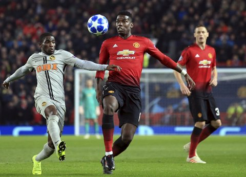 ManU midfielder Paul Pogba vies for the ball with Young Boys' Roger Assale, left, during the Champions League group H soccer match between Manchester United and Young Boys at Old Trafford Stadium in Manchester, England, Tuesday Nov. 27, 2018. (AP Photo/Jon Super)