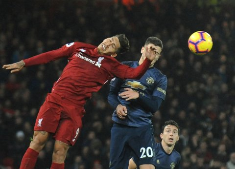 Liverpool's Roberto Firmino, left, and Manchester United's Diogo Dalot challenge for the ball during the English Premier League soccer match between Liverpool and Manchester United at Anfield in Liverpool, England, Sunday, Dec. 16, 2018. (AP Photo/Rui Vieira)