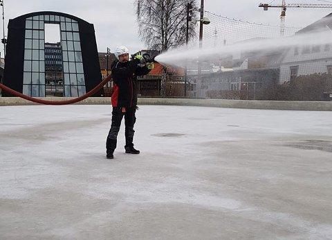 FULL SPRUT: Arbeidet med å lage skøyteis på Værstetorvet er i gang. Vaktmester Roy Saxvik Hansen håper å få isen seks centimeter tykk.