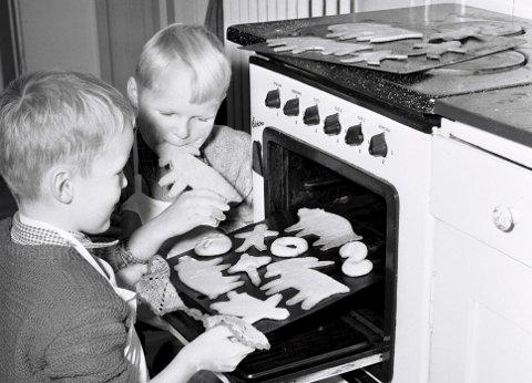 Velstandsutvikling og hjemmeværende husmødre gjorde etterkrigstiden til julekakebakstens storhetstid. Her er to smågutter i aksjon i 1954. Foto: NTB scanpix