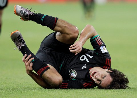 Mexico's Efrain Juarez falls after tripping over South Africa's Tsepo Masilela during the World Cup group A soccer match between South Africa and Mexico at Soccer City in Johannesburg, South Africa, on Friday, June 11, 2010.  (AP Photo/Themba Hadebe)