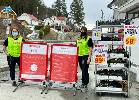 PASSER PÅ: Katarina Jokerud (t.v.) og Hege Helmerstuen ved Spar Noresund vil være godt synlige i gule vester og det er også satt opp store plakater med informasjon om smittevern.