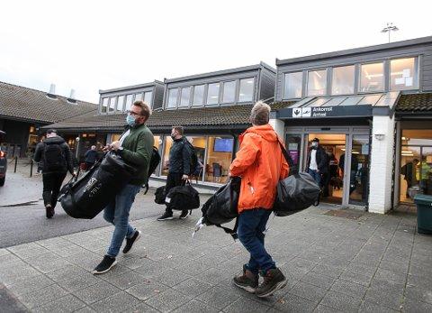 Ein gruppe offshorereisande har nettopp landa i Florø. Reisande nyttar munnbind som eit av smittevernstiltaka.