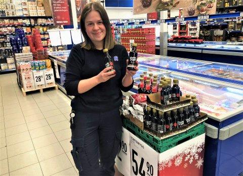 Kjersti Homb Jakobsen ved Rema 1000 Gjøvik Stadion holder fram de små flaskene med Tomtegløgg, de store er de tomme for.